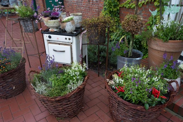 Alter Ofen zur Außendekoration mit Blumen und Kräutern