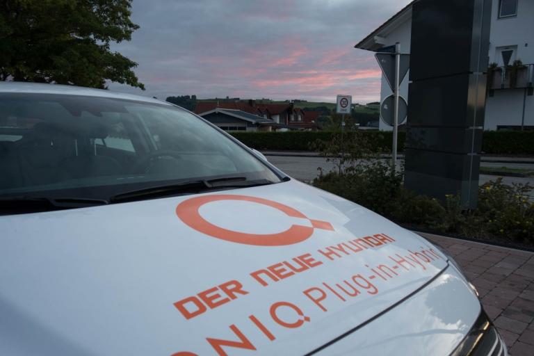 Hyundai IONIQ Plug-In Hybrid mit Sonnenuntergang im durch Kommissar Kluftinger bekannten Altusried